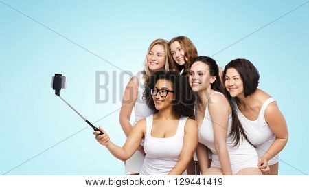 technology, friendship, body positive and people concept - group of happy women in white underwear taking picture with smartphoone on selfie stick over blue background