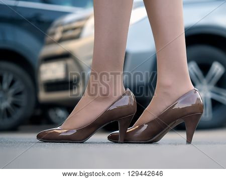 Women sumptuous legs in shoes on heels on car background
