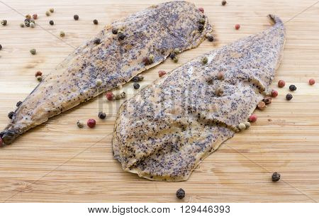 Two peppered mustard encrusted smoked mackerel on wood cutting board