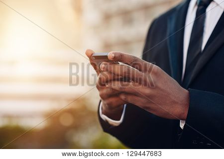 Cropped close up of the hands of an African businessman holding a mobile phone, wiht blurred city building in the background and soft sunflare