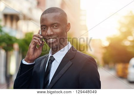 Portrait of a handsome young businessman of African descent smiling confidently at the camera, while holding his mobile phone to his ear and city buildings and sunflare in the background