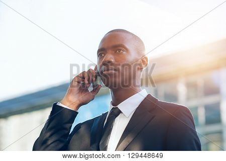 Young African businessman holding his phone to his ear and looking seriously into the distance with buildings and sunflare behind