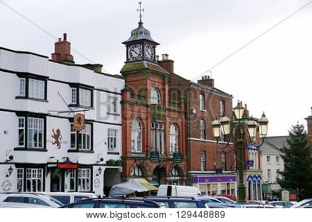 LEEK, UK - DECEMBER 31: Cars fill a small parking area outside a large public house and market building in the historic town of Leek, in the Staffordshire Moorlands, England on December 31, 2015.