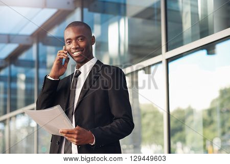 Young African businessman standing outside in front of the reflective windows of a big city building holding a file, and his phone to his ear while smiling at the camera