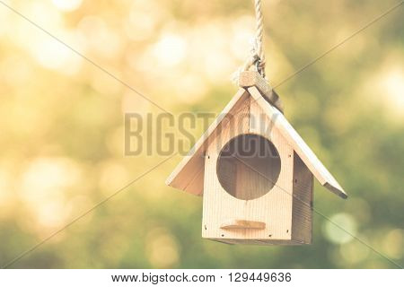 Bird house hung on the robe with green bokeh background