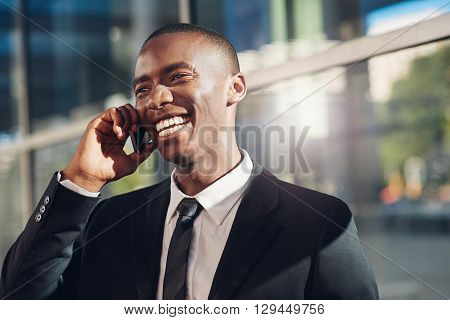 Handsome young businessman of African descent wearing a smart suit, holding his mobile phone to his ear and laughing with a friendly smile, while standing outdoors in a city