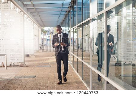 Full length shot of a young African businessman wearing a contemporary suit, walking past office windows on a city street, carrying coffee and looking at his mobile phone while reading a message