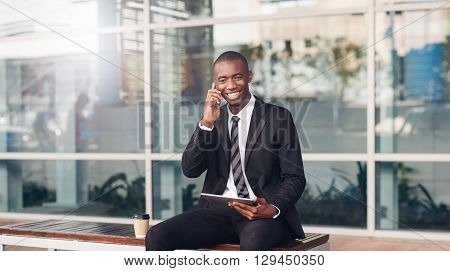 Handsome young African buisnessman sitting on a bench in the city, holding his digital tablet and smiling while talking on his phone