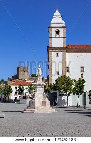Castelo de Vide, Portugal - July 24, 2015: Dom Pedro V Square in Castelo de Vide. Dom Pedro V statue with Santa Maria da Devesa church in the back. Alto Alentejo, Portugal