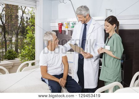 Doctor And Nurse Looking At Senior Patient At Rehab Center
