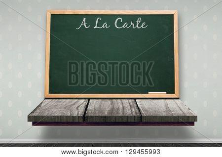 A la carte message against blackboard on a wooden shelf