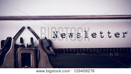 The word newsletter against white background against close-up of typewriter
