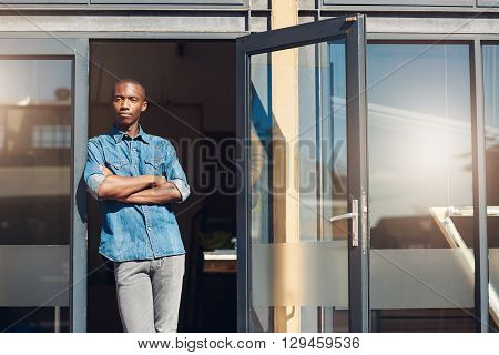 Handsome young African man who is a small business owner, standing with his arms crossed and leaning against the doorway of his design studio store