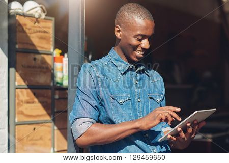 Smiling young designer of African descent standing in the doorway of his studio, smiling while using a digtial tablet