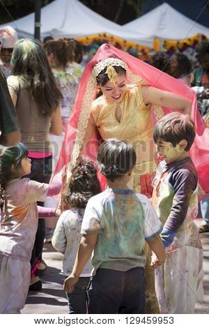 NEW YORK - APR 30 2016: A female member of NYC Bhangra dances with a group of young  children in the crowd at the Holi Hai Festival of Colors in Dag Hammerskjold Plaza in New York April 30, 2016.