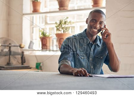 Potrait of a handsome young man of African descent sitting in his beautifully lit design studio, talking on his mobile phone about his small business, and smiling at the camera