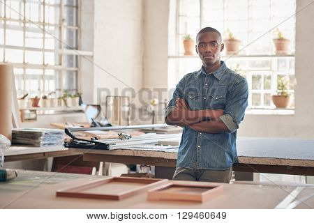 Young man of African descent standing proudly with his arms folded in the workshop where he runs his small business from, looking at the camera seriously