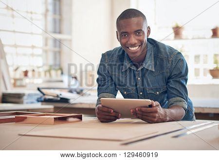 Smiling African small business owner, leaning on a work table in his studio, smiling at the camera while holding a digital tablet