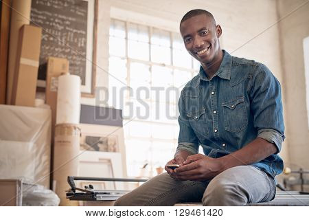Low angle portrait of a handsome young business owner of African descent, smiling at the camera while holding is mobile phone and sitting on a workbench in his studio workshop