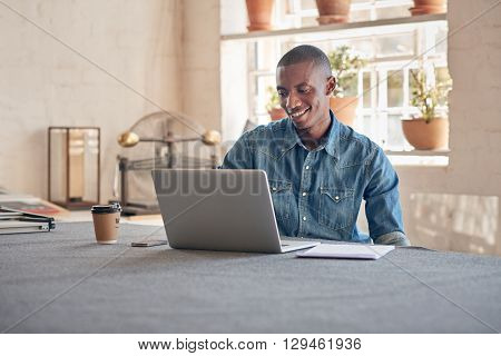 Young designer of African descent, in his design studio workshop with beautiful lighting, smiling while working on his laptop
