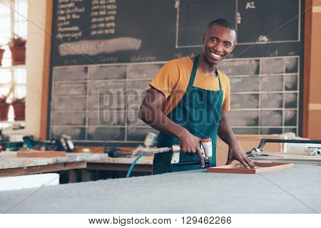Portrait of a handsome young craftsman of African descent working with a tool in a picture framing workshop, smiling broadly at the camera