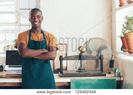 Confident young artisan of African descent, standing in his studio with beautiful light coming in through large windows, smiling handsomely with his arms folded
