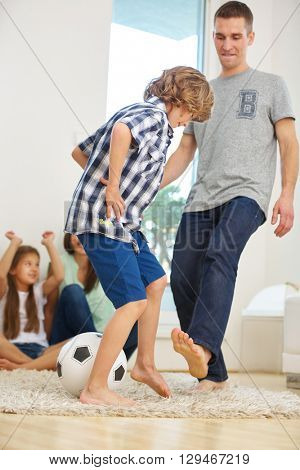 Father and son playing with soccer ball at home in the living room