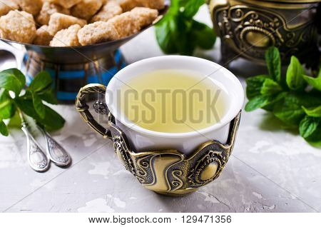 Freshly prepared mint tea out of fresh leaves in Oriental style on a concrete background. Selective focus.