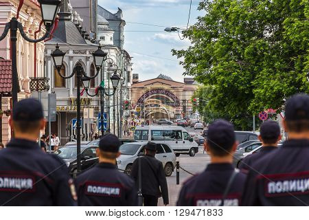 The photo shows the back of police patrolling the streets of Kazan the building of the central market theater advertising signs cars and city residents. The photo was taken in Kazan in the street Bauman June 11 2015.