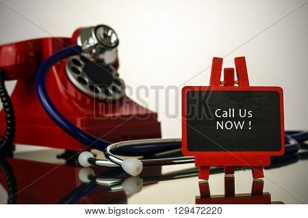 Medical Concept.phone And Stethoscope On The Table With Call Us Now Words On The Board.