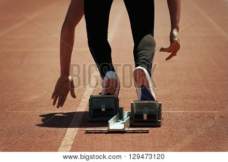 Sprint start in track and field.Shot of young male athlete launching off the start line in a race