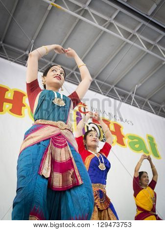NEW YORK - APR 30 2016: Female dancers from NYC Bhangra use mudras, or hand gestures, while performing on stage at the Holi Hai Festival of Colors in New York on April 30 2016.
