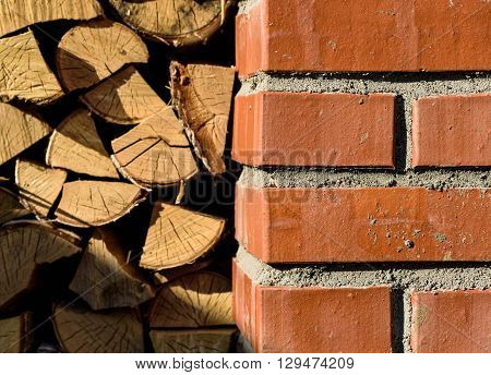 red brick woodshed on a background of stacked wood