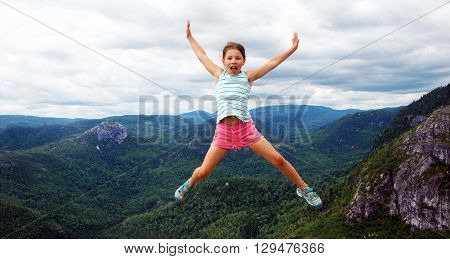 Picture of a girl jumping, on top of La Chouenne, in parc national des Grands-Jardins, Quebec, Canada.