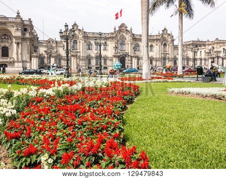 Lima, Peru - October 11 2014 - View of the Lima (Peru) Government Palace in a sunny spring day after a beautiful garden of red and white flowers.