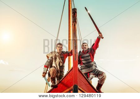 Two Warriors In Armor With The Swords On The Bow Of A Sailing Ship.