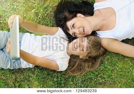 Happy Girl And Her Mother Having Fun And Taking Selfie On The Grass In The Park