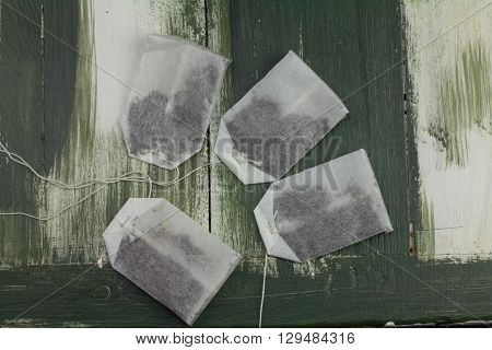 on a wooden board four unused tea bags