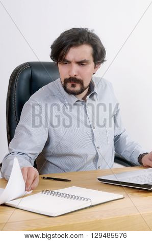 Portrait Of Attractive Serious Businessman Working With Documents At The Office