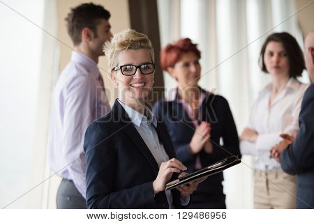 Smilling senior older  business woman with tablet computer  in front her team blured in background. Group of young business people at modern bright  startup office interior.