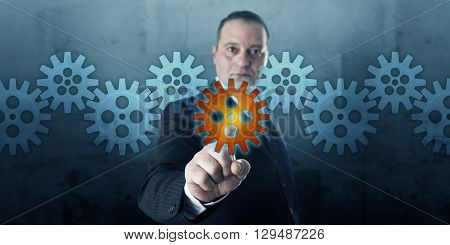 Male entrepreneur selecting a virtual cog wheel in a gear train line-up. The central gearwheel is lighting up via touch or click. Business metaphor for mechanics of corporate or physical processes.