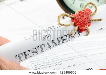 Man holding a rolled up scroll of last will and testament fastened with natural brown jute twine hemp rope sealed with sealing wax and stamped with alphabet letter B.