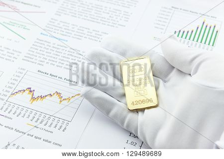 Man right hand with a white handy glove is showing / presenting an one ounce gold bar to a customer for inspection. A gold ingot in a hand on a table with many financial and business analysis reports.