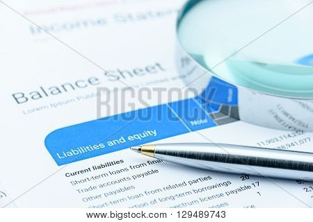 Blue ballpoint pen on a firm's balance sheet in the section of liabilities and equity with a magnifier. In-depth financial analysis for long term sustainable investment for value investor concept.