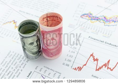 Rolled up scrolls of US dollar bill and Chinese Yuan with image / portrait of President Mao Zedong and Benjamin Franklin. Placing on financial reports with several charts i.e. colored linear graph.