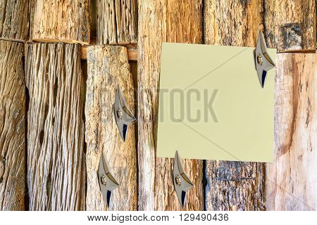 Blank piece of paper attached on an old wooden wall with Japanese ninja weapons. Copy space for leaving several messages when you are absent i.e. info news suggestion recommendation notice etc