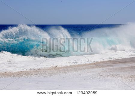 Beautiful and powerful Pacific ocean wave with foam on shore.