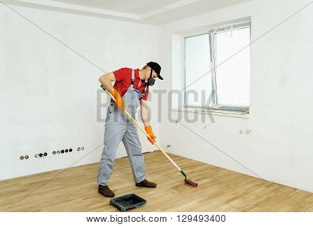 Lacquering wood floors. Worker uses a roller to coating floors.