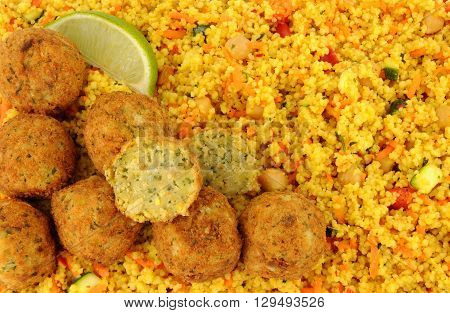 Vegetarian fried falafels on a couscous background with fresh lime wedges