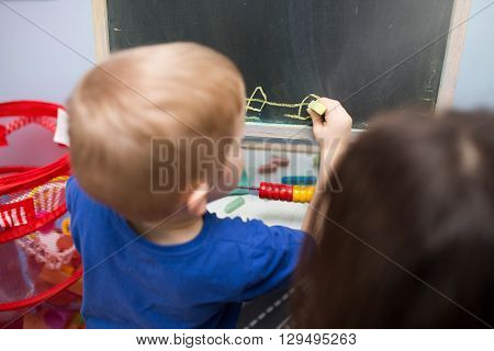 A photo of small boy chalking on the blackboard. He's being watched by his teacher.